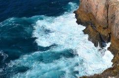 Strong waves in blue sea. Splashing on big rocks Stock Images