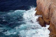 Strong waves in blue sea. Splashing on rocks Stock Photo