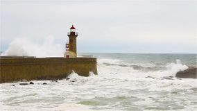 Strong waves break about the pier, the lighthouse on the shore of the Atlantic Ocean stock video