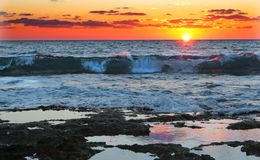 Strong waves at orange sunset Royalty Free Stock Photos