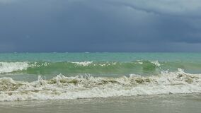 Strong white waves of blue sea slowly running to sandy beach against stormy sky. Strong white waves of blue sea slowly running to sandy beach against dark stormy stock footage