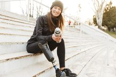 Strong willed handicapped woman in black tracksuit with prosthetic leg laughing, while sitting at the street stairs with thermos. Strong willed handicapped woman royalty free stock photos