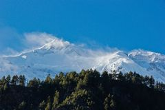 Strong wind in Himalaya / Nepal. Landscape in Nepal / Himalaya in summer on the tree line with beautiful peaks full of snow on blue sky royalty free stock images