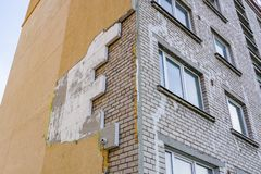 Strong wind or poor quality of work damaged building thermal insulation. Strong wind or poor quality of work damaged apartment building thermal insulation royalty free stock photos