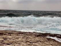 Big powerful waves crashing on Croatian shore. Strong wind and waves splashing on the beach royalty free stock images