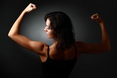 Strong woman. Strong brunet woman demonstrating her muscules. Studio profile portrait against black background Stock Photography