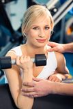 Strong woman. Photo of strong woman lifting dumbbell and looking at camera Stock Photography