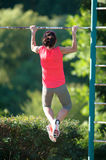 Strong woman athlete is Chin-ups and Pullups training on an abandoned sports field. Pull-up on the bar. Athlete Outdoors. royalty free stock photo