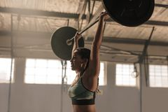Female athlete lifting heavy weights. Strong woman with barbell overhead doing exercise. Fit female athlete lifting heavy weights stock images
