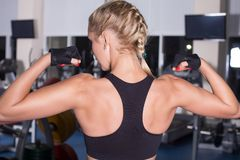 Strong woman with beautiful body shows her muscles. Workout in gym Royalty Free Stock Image