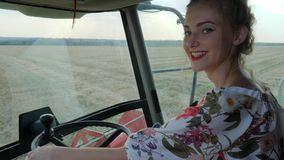 Strong woman behind wheel of Combine harvester in field in Bread harvest season. Strong woman with red lips laughs behind wheel of Combine harvester in field in stock video footage