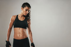 Strong woman in black athletic garments stands Royalty Free Stock Images