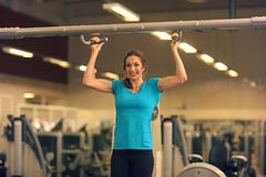 Strong woman in blue t-shirt and black pants exercising in a gym - doing pull-ups. Royalty Free Stock Photography