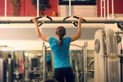 Strong woman in blue t-shirt and black pants exercising in a gym - doing pull-ups. Royalty Free Stock Images