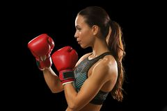 Strong woman in boxing gloves. On black background Stock Photography