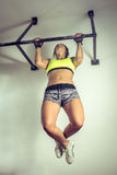 Strong woman doing pull ups. Strong young adult woman doing pull up exercise indoor stock photo