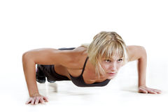 Strong woman doing push-up. On a white background stock photo