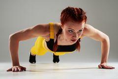 Strong woman doing push-ups. In studio Royalty Free Stock Photo