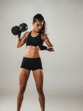 Strong woman doing shoulder press with dumbell Stock Photos