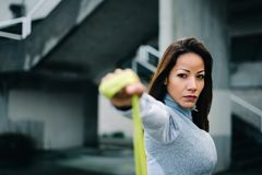 Strong woman doing shoulder raises exercise with resistance band. Motivated latin woman doing shoulder raises exercise with fitness resistance band. Urban Stock Images