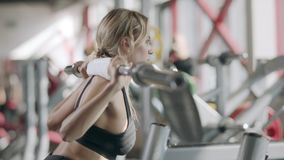 Strong woman doing squat exercise with barbell in fitness center. Closeup fitness woman squatting with barbell at bodybuilding training. Blonde girl lifting stock video footage