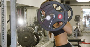 Strong woman doing squats workout with heavy weights