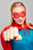 Strong woman dressed as a superhero for carnival. Strong woman dresses as a superhero for carnival clenching her fist royalty free stock photo