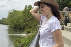 Strong Woman next to river with hat stock image
