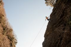 Strong woman equipped with a rope abseiling on the sloping rock. Strong woman in the pink top and black pants equipped with a safety rope abseiling on the stock photography