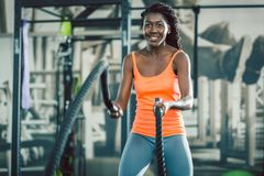 Strong woman exercising with battle ropes during functional training. Low-angle view of a strong and beautiful African American woman, exercising alternative royalty free stock image