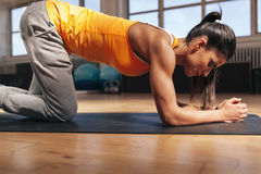 Strong woman exercising on fitness mat royalty free stock photography