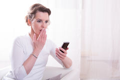Strong woman is frightended by message on smartphone Royalty Free Stock Image