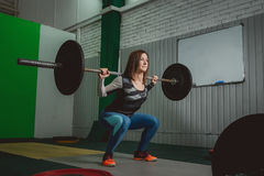 Strong woman lifting barbell as a part of crossfit exercise routine Royalty Free Stock Images