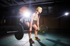 Strong woman lifting barbell as a part of crossfit exercise routine. Fit young woman lifting heavy weights at gym. royalty free stock photos