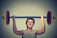 Strong woman lifting heavy barbell. Royalty Free Stock Photography