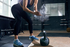 Strong Woman Lifting Kettlebells in Gym stock images