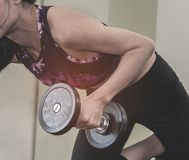 Strong woman lifting a weight dumbbell with her left arm. Strong woman is lifting a weight dumbbell with her left arm Stock Photo