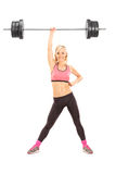 Strong woman lifting a weight with one hand. Full length portrait of a strong woman lifting a weight with one hand isolated on white background Stock Photography