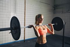 Strong woman lifting weights in crossfit gym. Fitness woman concentrating while lifting barbells. Strong woman lifting weights in crossfit gym. Caucasian female Royalty Free Stock Photos