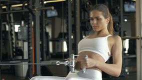 Strong woman lifting weights on training equipment in fitness club stock video