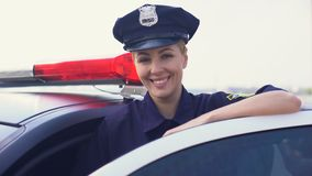 Strong woman in police uniform standing near patrol car smiling, law and order stock video footage