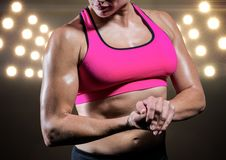 Strong woman posing against black illuminated background royalty free stock photography