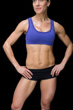 Strong woman posing in sports bra and shorts with hands on hips Stock Image