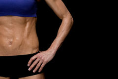 Strong woman posing in sports bra and shorts mid section Royalty Free Stock Photo