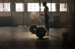 Strong woman preparing for weightlifting workout. Strong young woman about to lift heavy weights at gym. Fitness female doing workout stock images