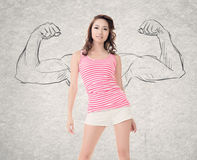 Strong woman. Pretty young woman with sketched strong and muscled arms on background royalty free stock photos