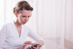 Strong woman is reading message on smartphone Stock Photos