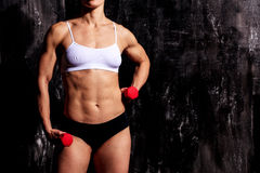 Strong woman with red barbells. Dark background Royalty Free Stock Photos