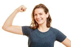 Strong woman shows muscles with power. Strong woman shows her arm muscles with power Royalty Free Stock Images