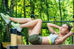 Strong woman in sportswear goes in for sports outdoors. In the park royalty free stock photography